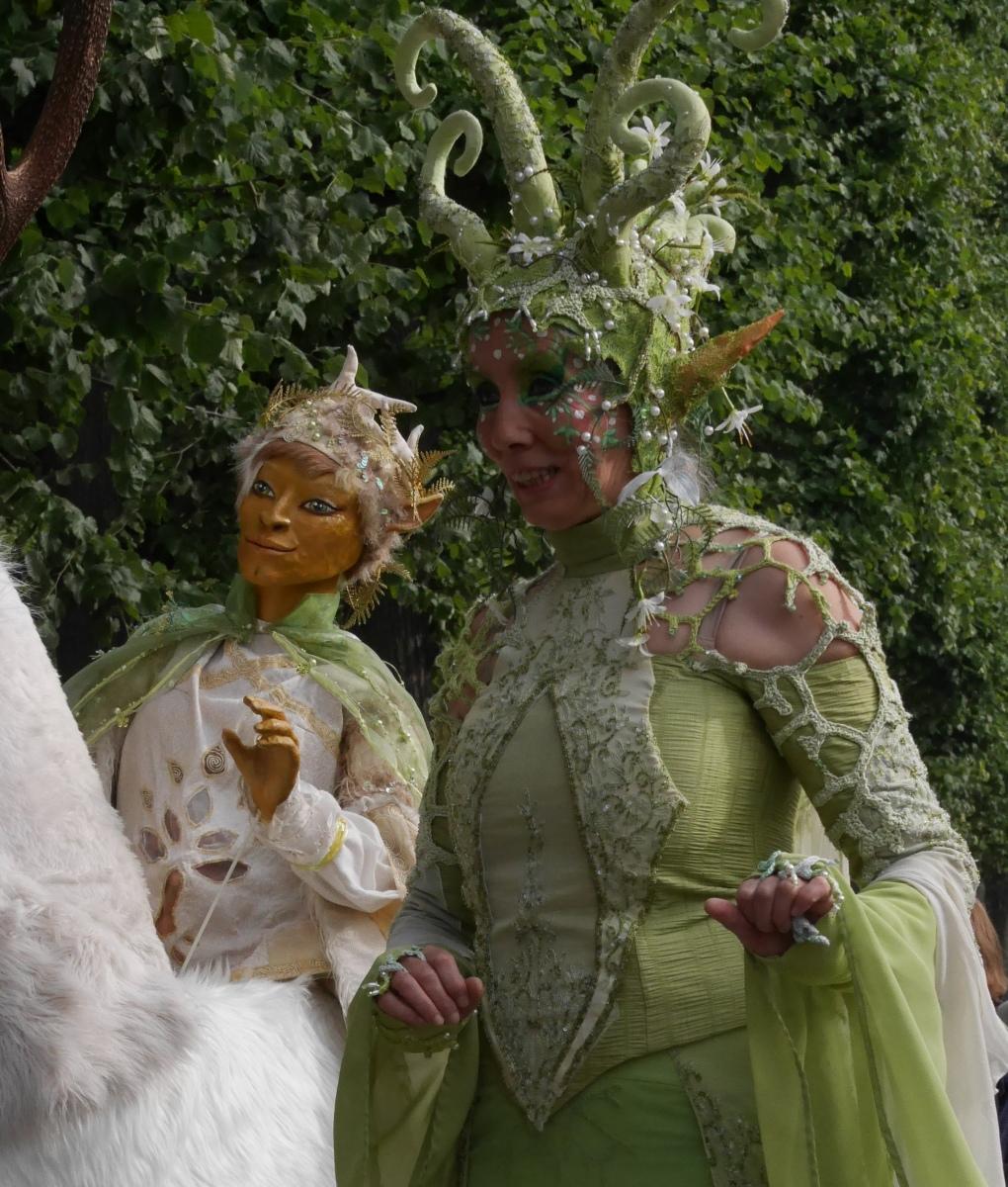 Eine Elfe wird von einem auf einem weißen Hirsch reitenden Elf begleitet.