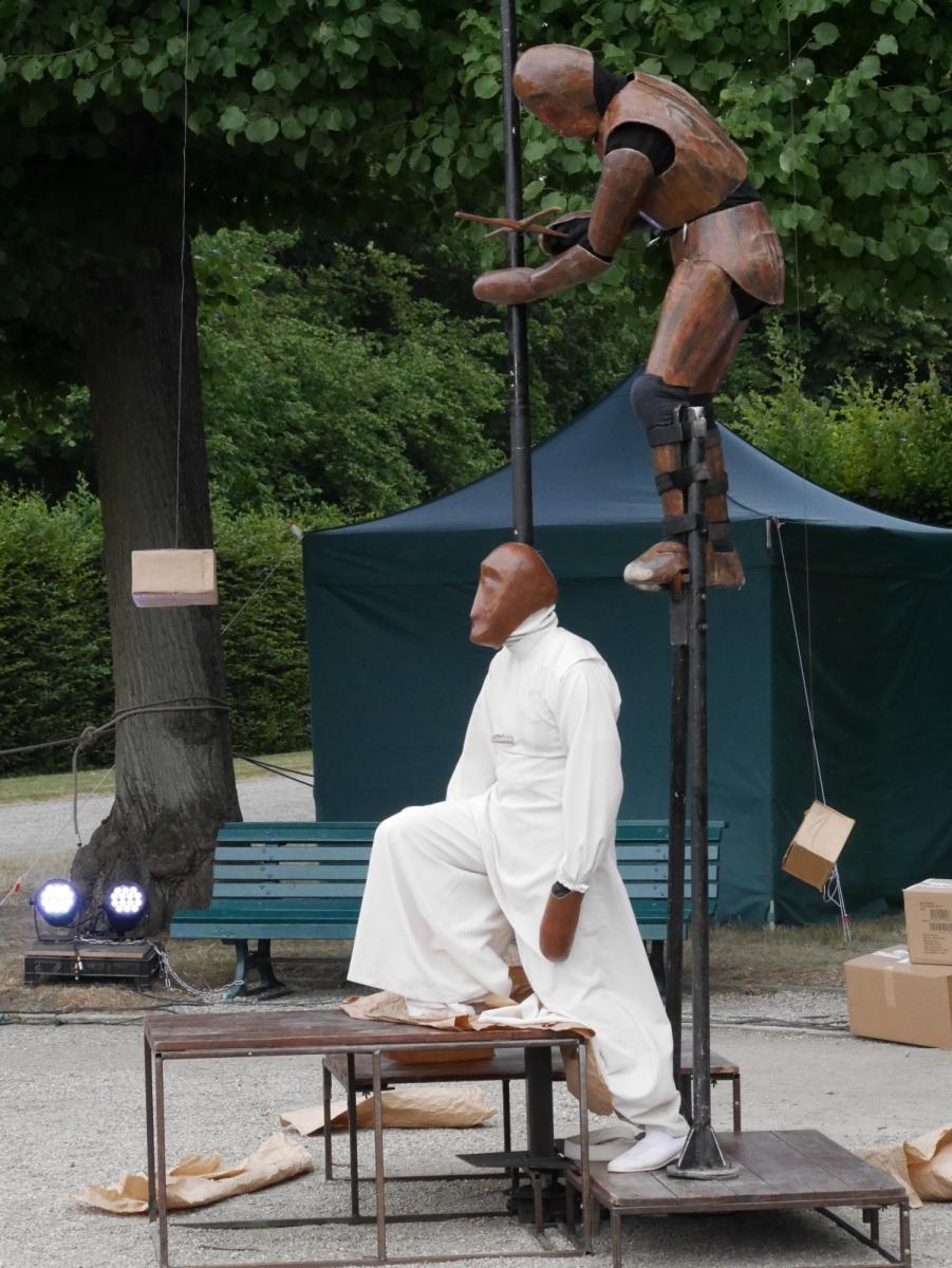 Zwei grob gestaltete Figuren gehen eine Beziehung ein, wobei die Weiße als Marionette der Metallfigur agiert.