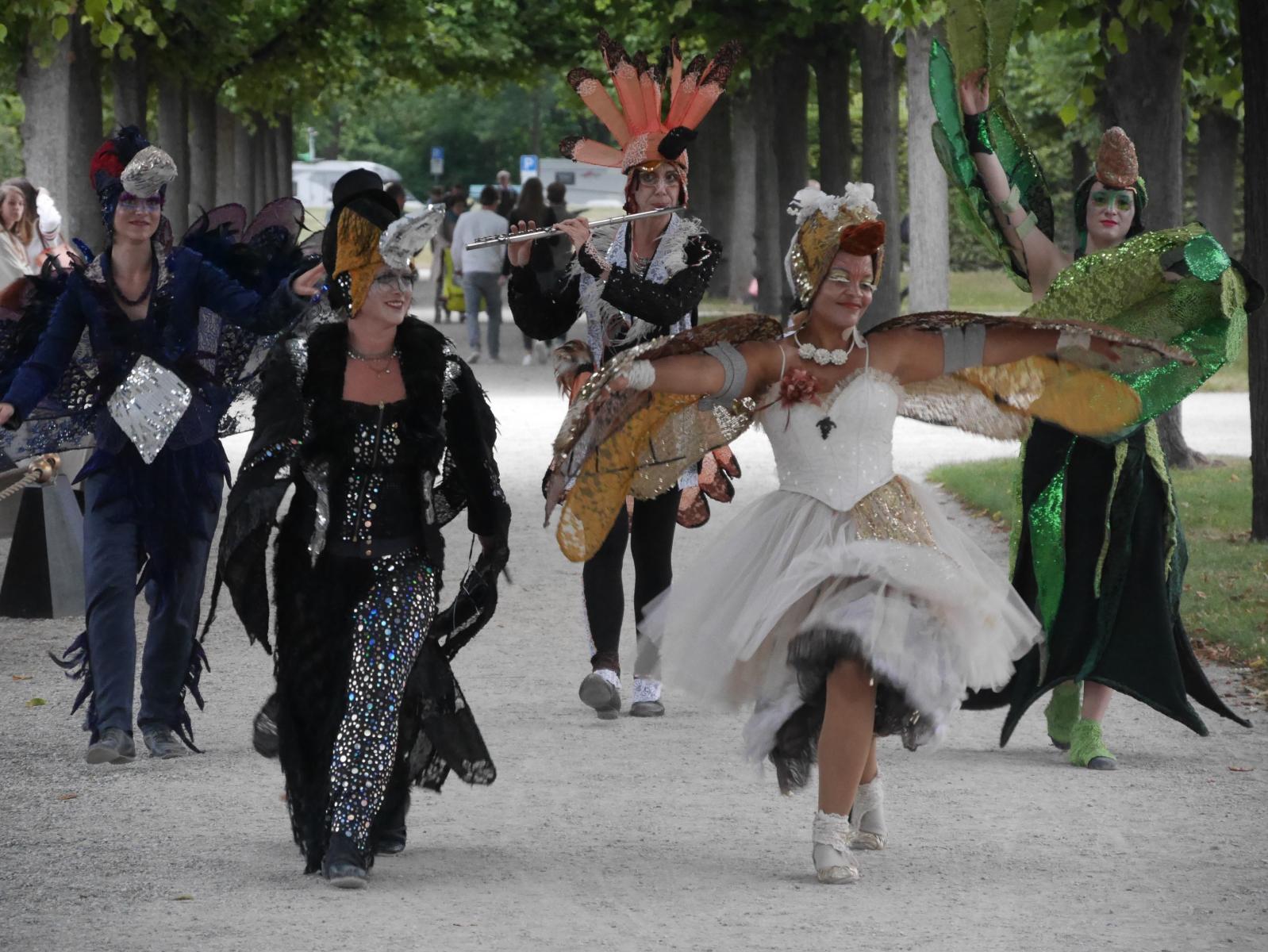 Spielende und tanzende Phantasievögel schreiten über die Wege der königlichen Gärten von Herrenhausen.