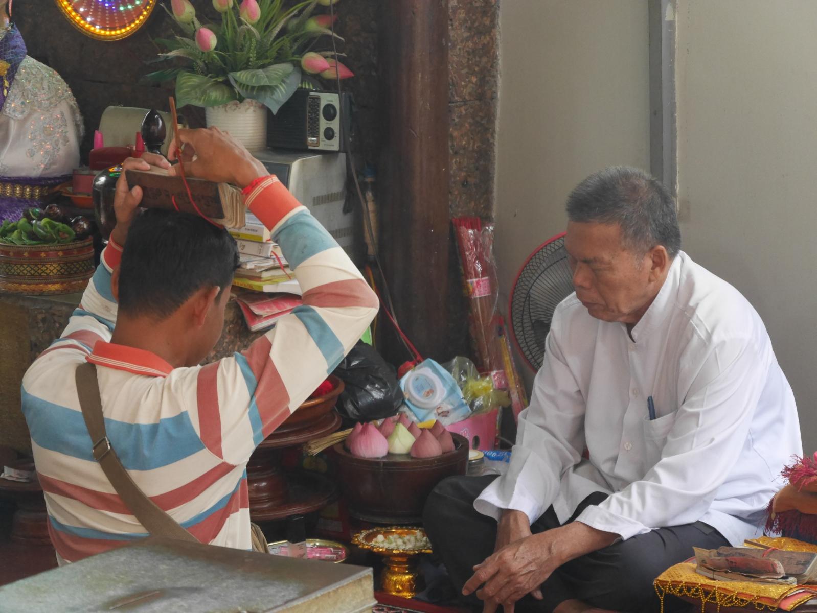 In einem Tempel findet ein Ratsuchender traditionelle Unterstützung. Ein Wahrsager deutet ihm die Textstelle, die auf seine Frage Antwort gegen soll.