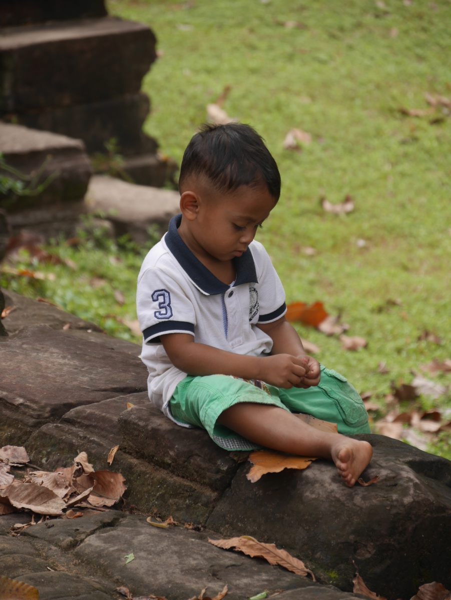 Ein kleiner Junge sitzt auf einer Mauer vor den Tempelanlagen von Angkor.