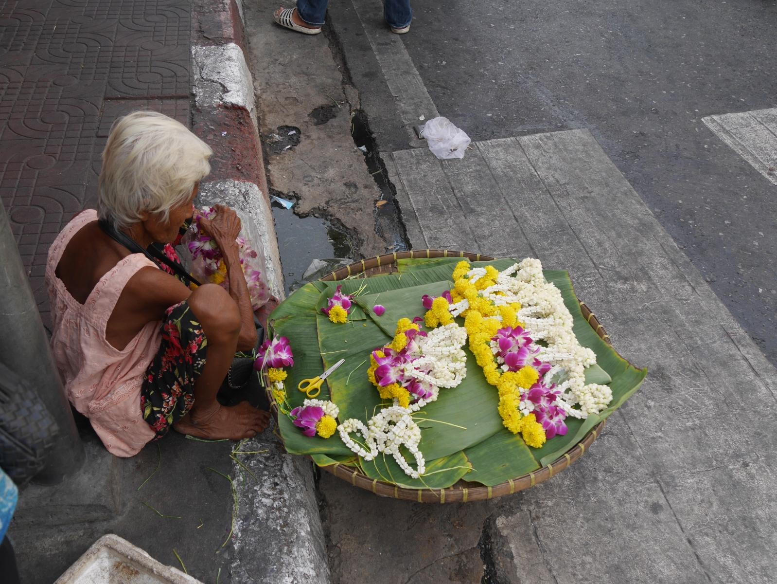 Eine Bettlerin verkauft  Jasminblütenkettchen für die Tempelopfergabe.