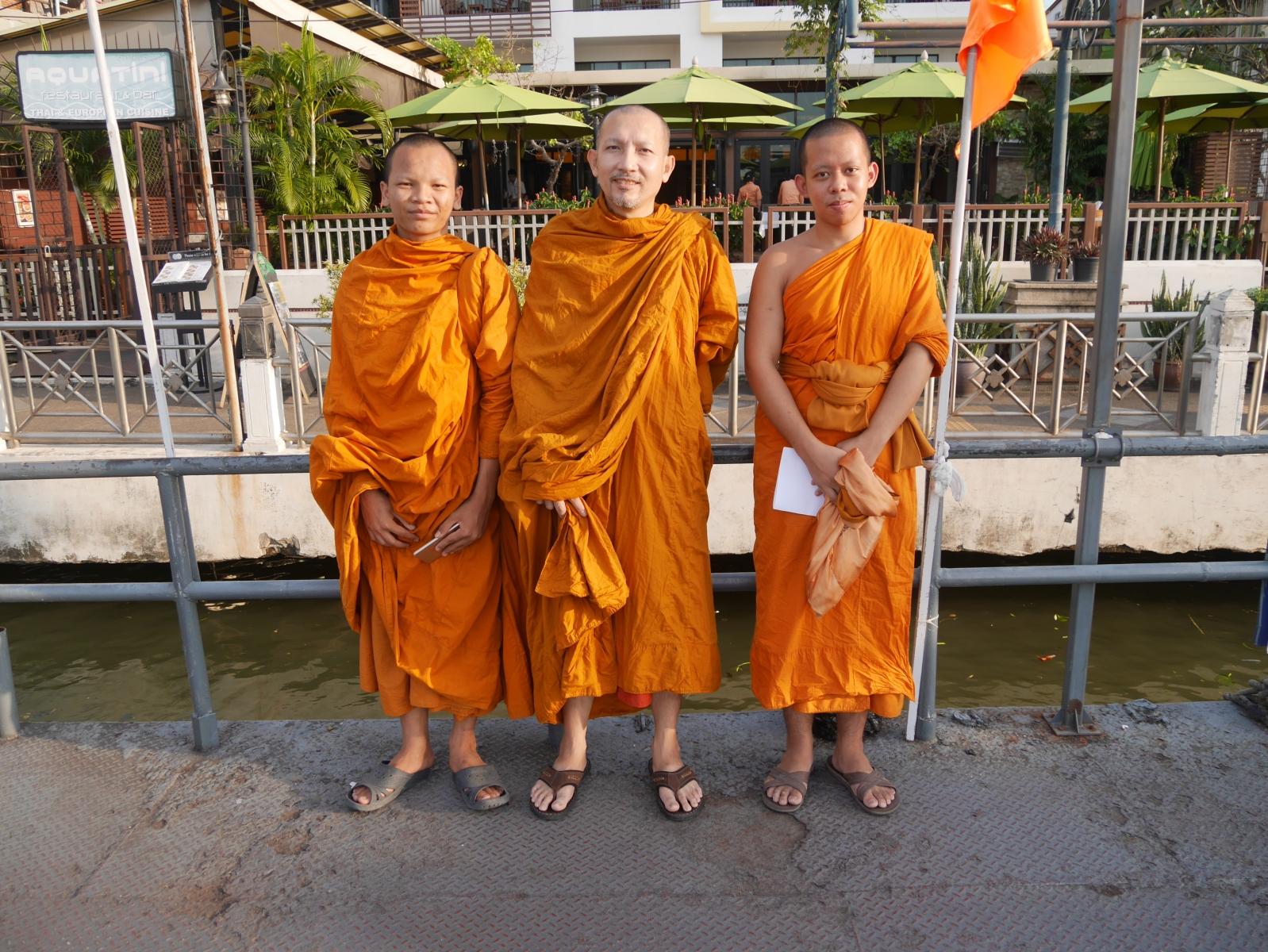 Drei Mönche fahren mit dem Boot auf dem Chao Phrayal zu einem Kloster.